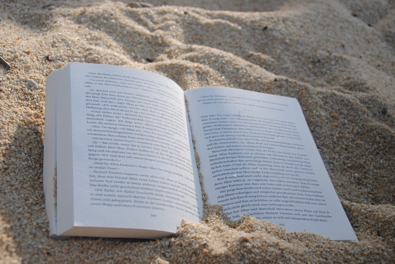 book in beach sand
