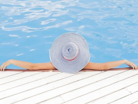 woman in pool in large sun hat