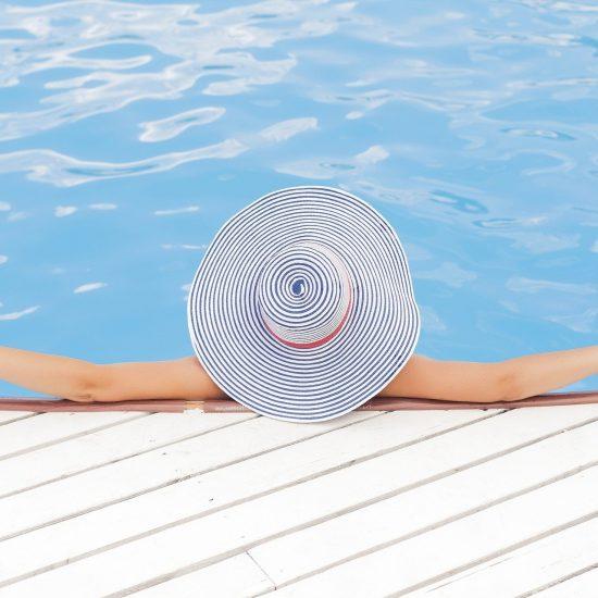 woman in pool in large sun hat
